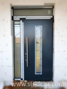 Двері Hörmann Thermo65 в мотиві 700 та кольорі Антрацит (Ral 7016). Двері змонтовані з бічним елементом та фрамужним вікном.